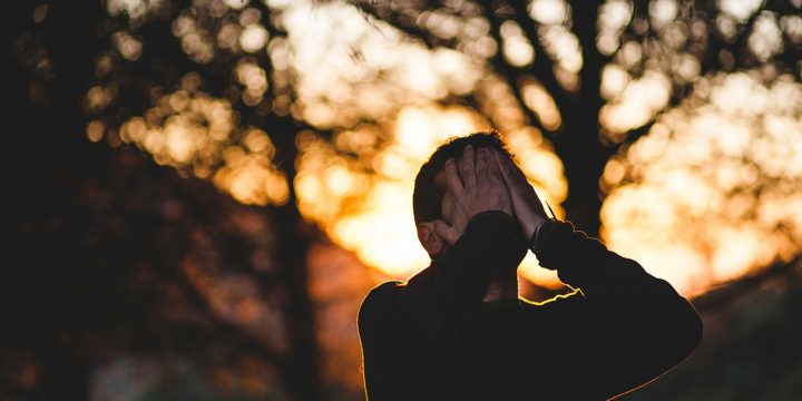 Photo image of man crying in the woods.